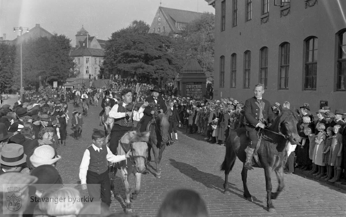 Folk i bunad og til hest paraderer gjennom sentrum. Felespiller i front.
