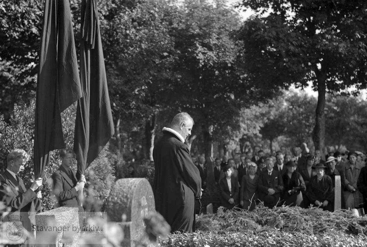 Presten står ved graven under bisettelsen. Røde flagg i bakgrunnen.