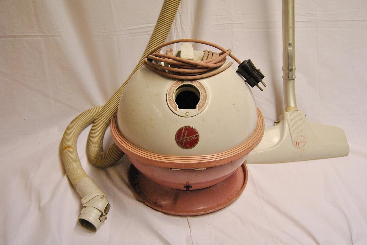 Hoover Constellation, modell 862. Rund maskin med fot. Håndtak på toppen av maskinen og festet til slangen på siden. Slange med munnstykke. Slangen er reperert med teip et par plasser.