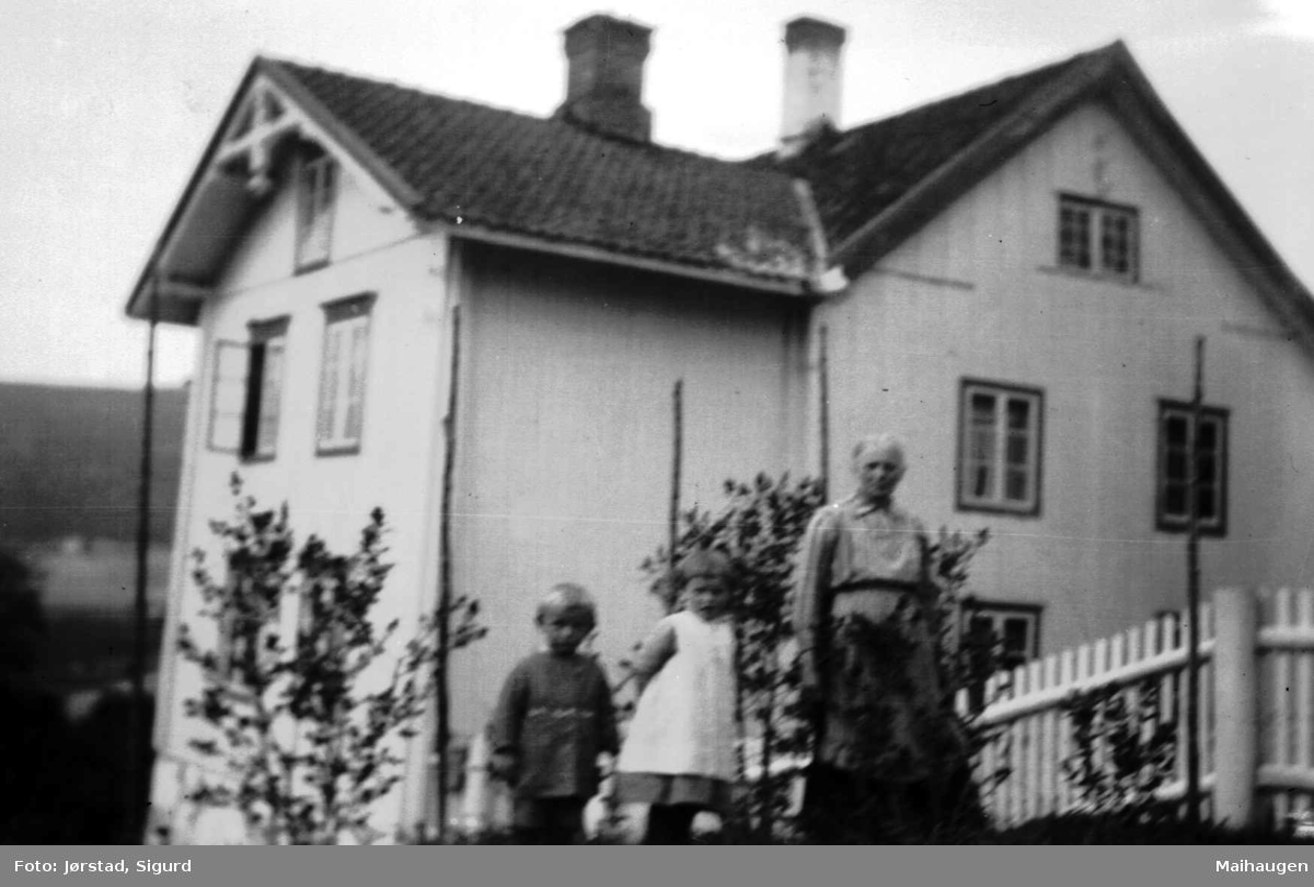 Kvinne med to barn utenfor et hus