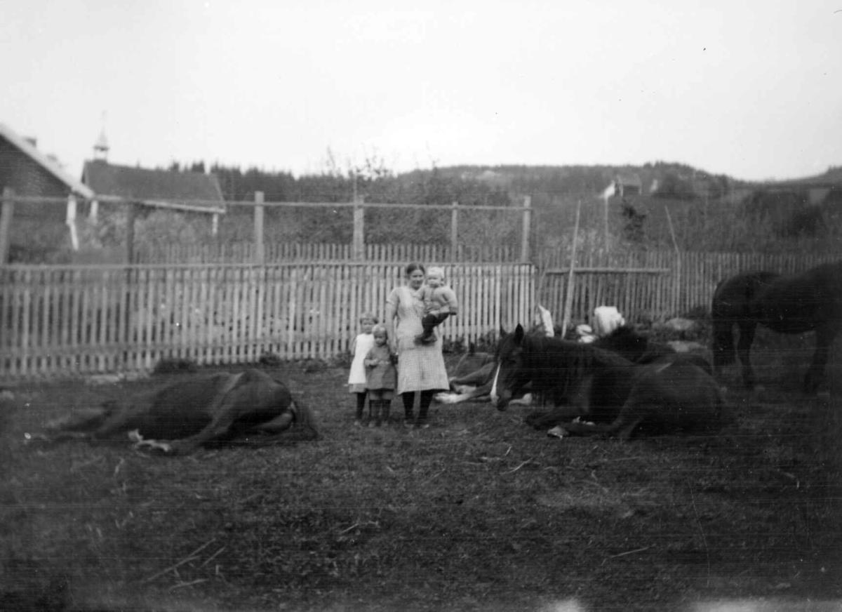 Kvinne med tre barn og hester ved Jørstad Søgarden.