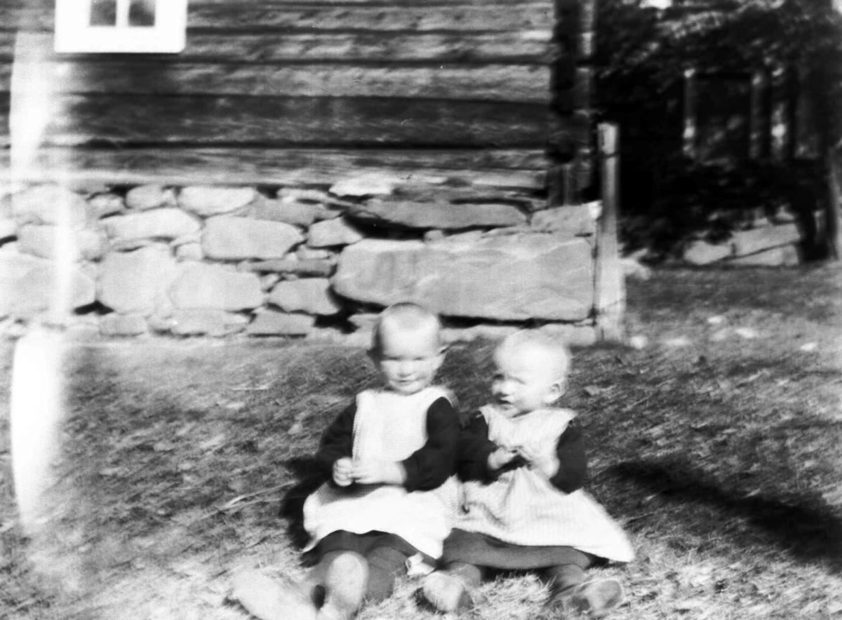 To småbarn utenfor en tømmerbygning.