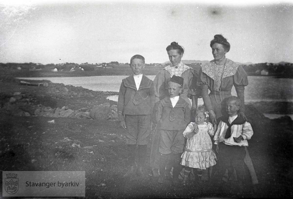 To kvinner og fire barn ved vann
