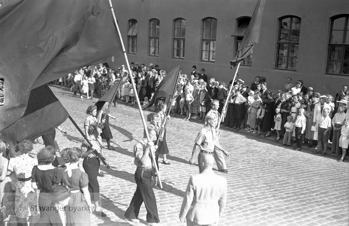 Arbeiderpartiets jubileumsdemonstrasjon.Tog med røde faner passerer tilskuere langs posthuset.