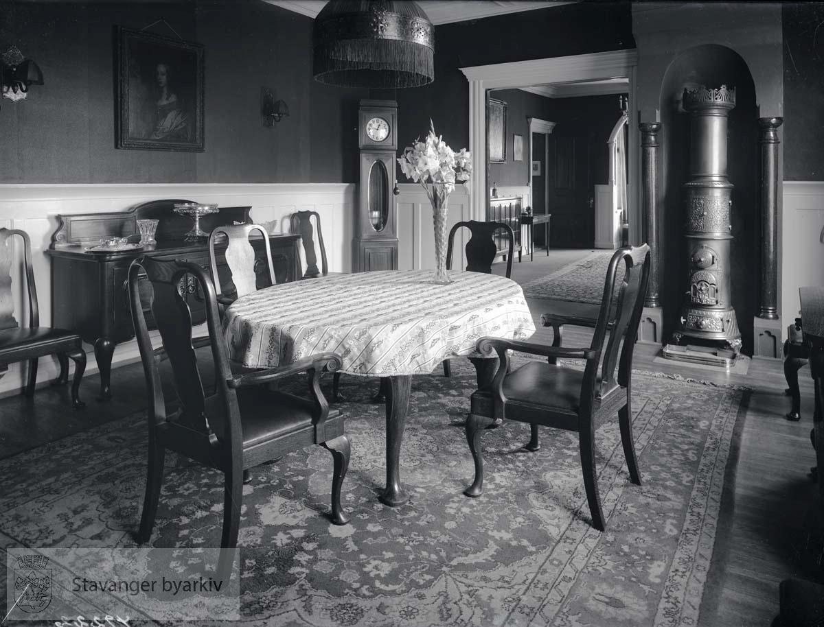 Stue med spisebord. Støpejernsovn og klokke i bakgrunnen. Villaen tilhørte den gang konsul Brehmer.