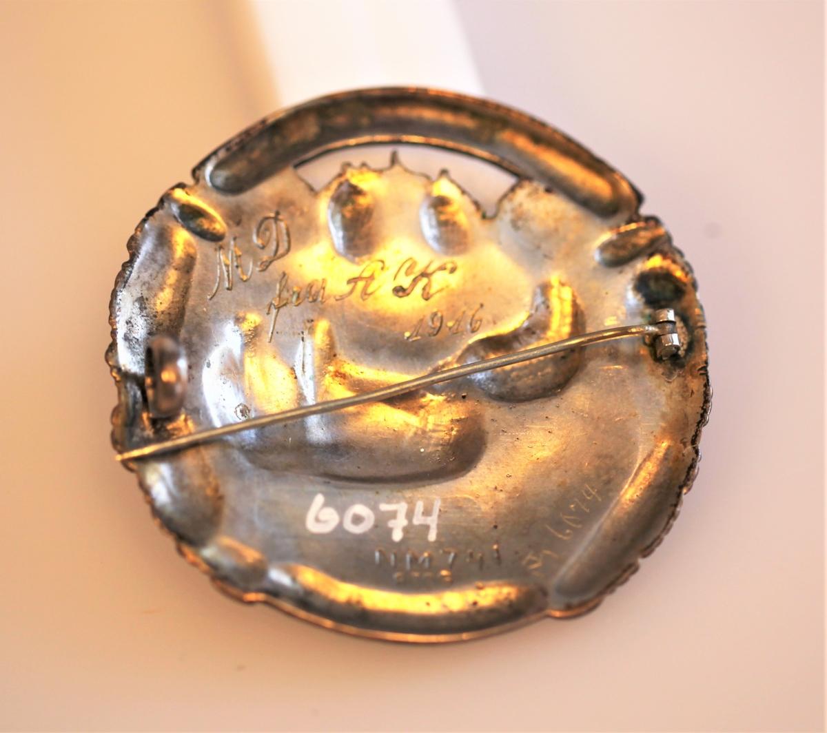 Sirkelrund og støpt brystnål med bilder og innskrift i relieff. Motivet er Sverdrups ferd til riksforsamlingen på Eidsvoll i 1814, han kjører i spisslede godt nedpakket under sledefellen, Kjørekar bakpå med tommene i venstre og svepen i høyre hånd , i bakgrunnen Eidsvollbygningen. Over langs kanten står TIL RIGSFORSAMLINGEN 1814, under langs kanten HUSK GUD ER ATAAT, mellom inndkriftene sammenfattede hender. Bak på nålen MD fra AK 1916 N M 741 830S