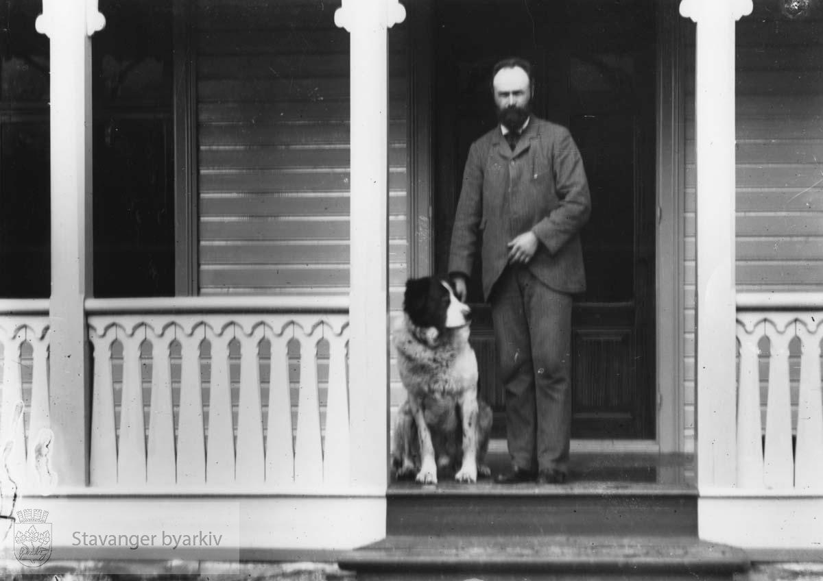 Blidensol. Mann med hund på terassen foran døren
