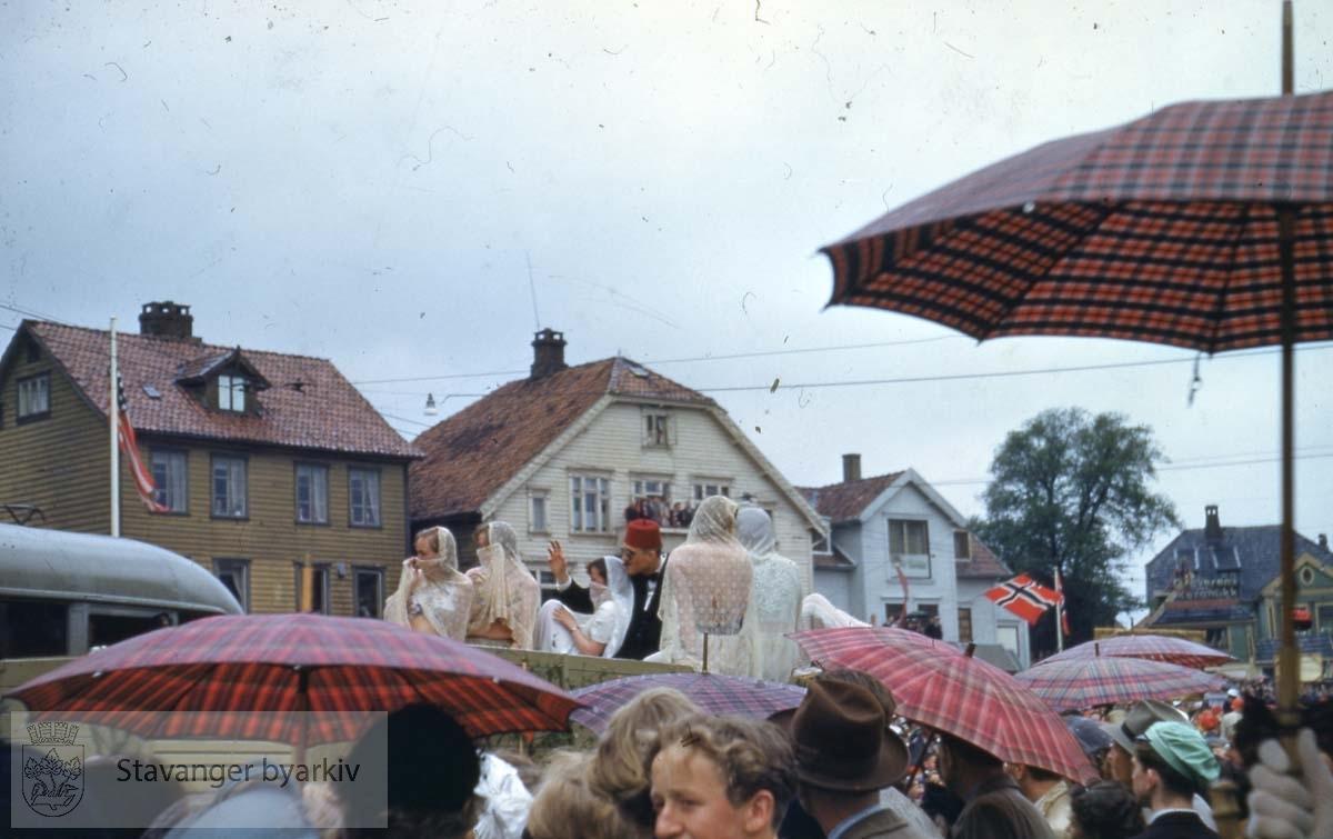 """Folk med paraplyer ser på """"sjeik"""" med harem."""