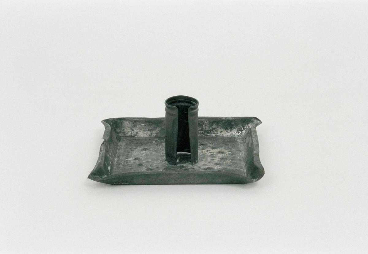 Ljusstake (ljusplåt) av bleckplåt, 4-sidig platta med utdragna hörn och punktdekor, en ljuspipa.