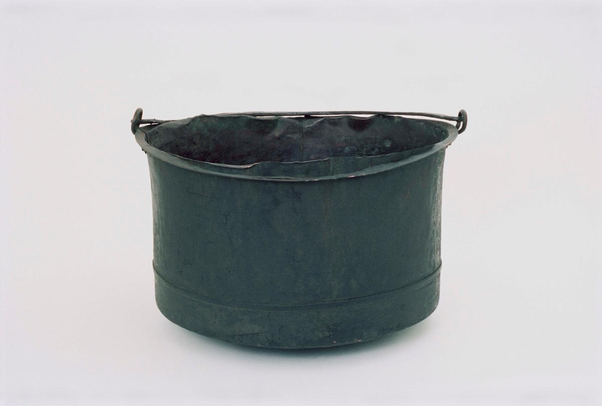 Gradbottnad kittel av koppar, förtennad, lös tvärgrepe av smidesjärn, avlånga grepfästen, utvikt mynningskant.