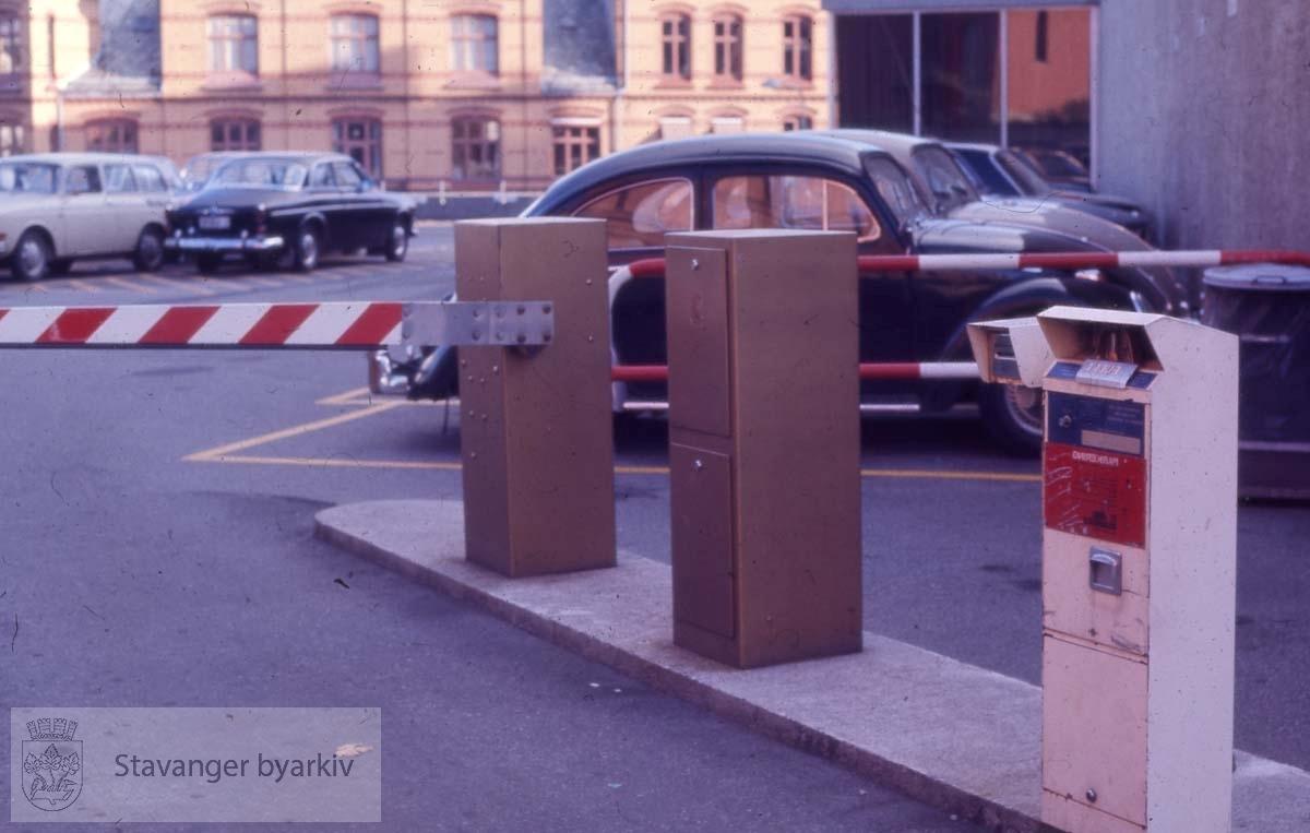 Parkeringsbom og automat.Myhregården i bakgrunnen