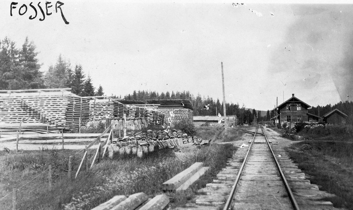 Ved- og plankelagre som venter på transport, trolig under krisen i 1918. Stolper for elektrisk belysning er under montering.