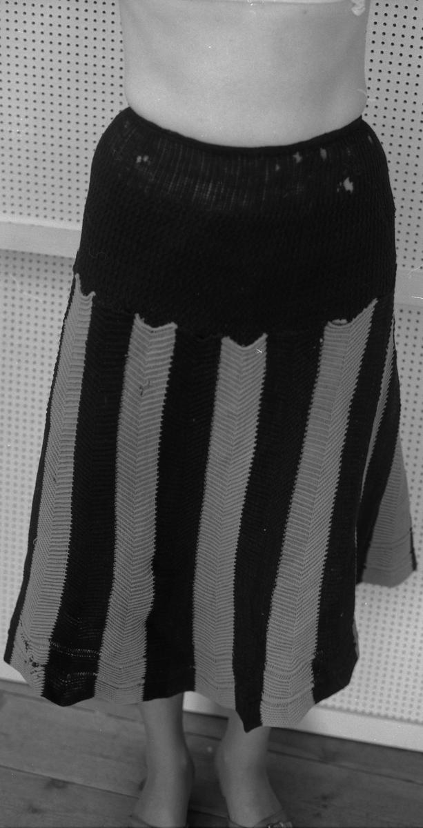 Underskjørt.  Gård og bygd:Gruset, Grue.  Mottatt:B. Falckners dødsbo v/Tvengsberg.  I hoftestykket 20 cm bredt ensfarget svart.  Fra hoften og ned langsgående svarte og rosa striper, ender i tunger øverst ca. 6 cm bred og nederst 9.