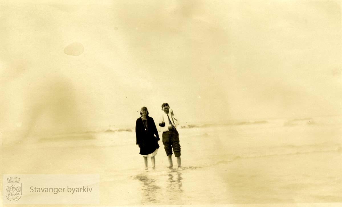 Mann og dame vasser i vannet ved en strand