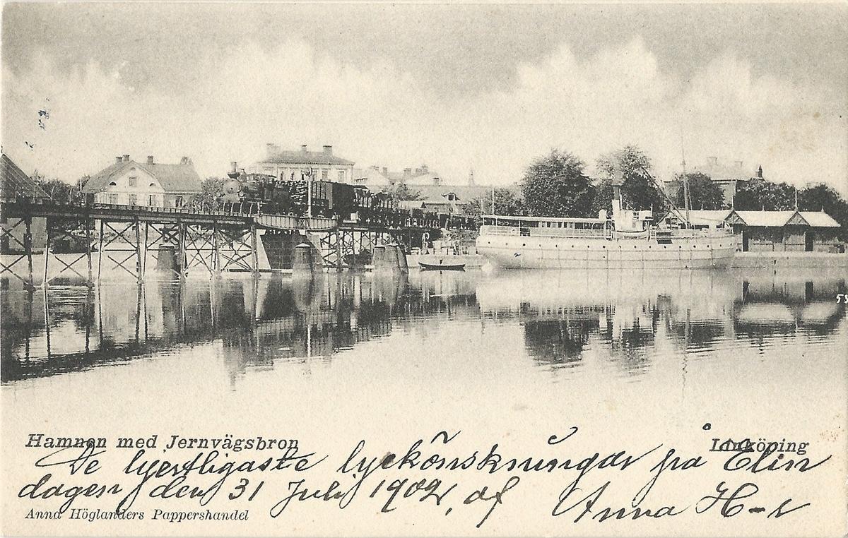 Vykort från  Linköping hamnen med järnvägsbron över Stångån. hamnen, järnvägsbron från väster,tullkontor, ånglok, Kinda kanal, Stångån, fraktfartyg,  Poststämplat 30 juli 1902 Anna Höglanders pappershandel