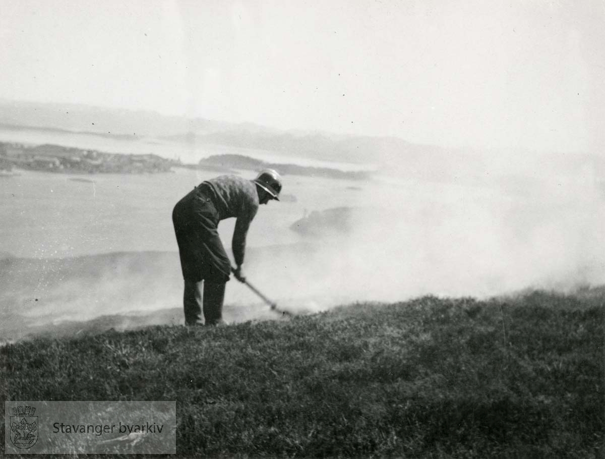 Brannmann slukker gressbrann.