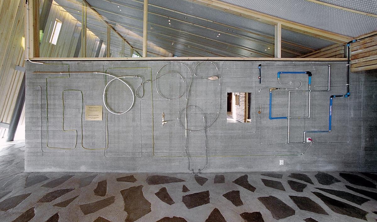 På den store pussede betongveggen i byggets foajé møtes industrielt fremstilte rør og ledninger, kabler og koblinger med hverdagsgjenstander som et messingdørhåndtak, en stikkontakt og et speil samt elementer funnet i naturen, som et vakkert skjell og bambus- og trestykker. Rørene er malt blå, gule og grønne flere steder, og reflekterer lyset fra de tilsvarende fargede vindusglassene i bygget. Installasjonen har en labyrintisk struktur med forgreninger i flere retninger langs tilstøtende vegger. En av grenene runder et hjørne og ender i en pilspiss som har tilhørt kunstneren selv. En annen bryter gjennom bygningsmuren og kryper videre langs bakken over en stor stein før den forsvinner ned i jorden.  Hvorvidt verket begynner ute og arbeider seg innover i bygget eller omvendt – hva som er sentrum og hva som er periferi – forblir et åpent spørsmål. En pekepinn om lesemåter får man på en messingplate på fondveggen. Her er et indiansk ordtak risset inn på samisk og norsk: «Det er syv hovedretninger: Opp, Øst, Sør, Nord, Vest, Ned og Inn i Deg Selv.»