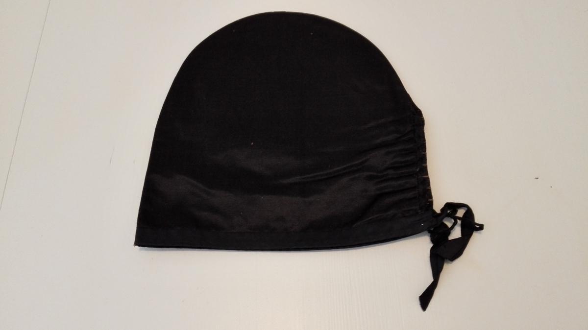 Svarthue: Sjå omtale av svarthue på nr. 6100.   6103 - Av sort klæde, kantet med sorte baand, foret med sort tøi.           Har løs papriform.  Kjøpt paa auktion paa Storaker i Hyllestad ved lensm. A. Faleide.