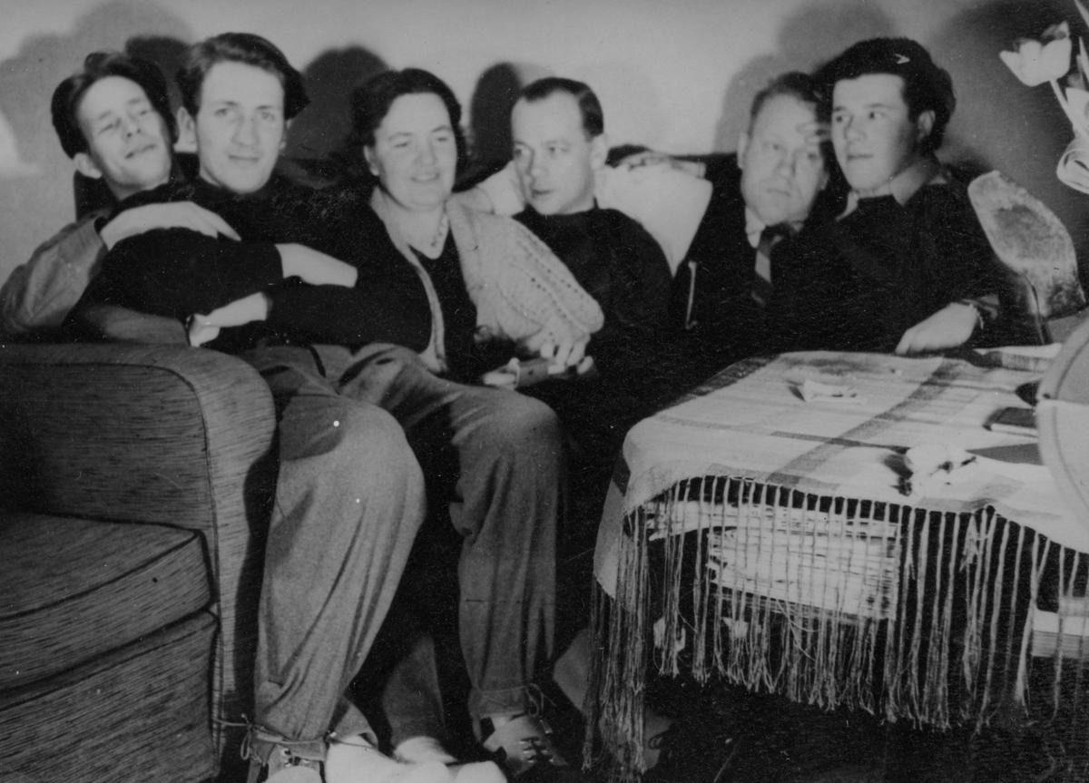 Samkväm på förläggning vid Svenska frivilligkåren i Finland, F 19. Gruppfoto av fem militärer och en kvinna sittande vid ett festbord. Från vänster: Matti Sundsten, Roland Sahlberg, okänd kvinna, okänd man, okänd man, okänd man.