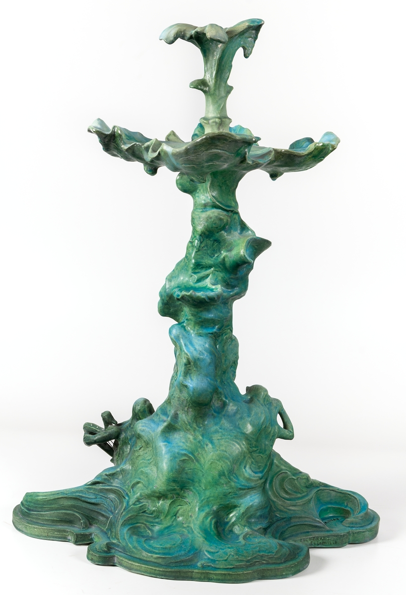 Bordsuppsats signerad Ida Matton. Tillverkad i Paris. Porslin med grön glasyr. Föreställer näcken spelande på harpa vid ett vattenfall.
