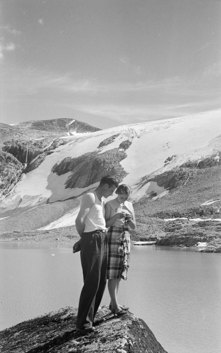 Kvinne og mann på utsiktspunkt i fjellet, antakelig langs veg fra Østlandet til Vestlandet