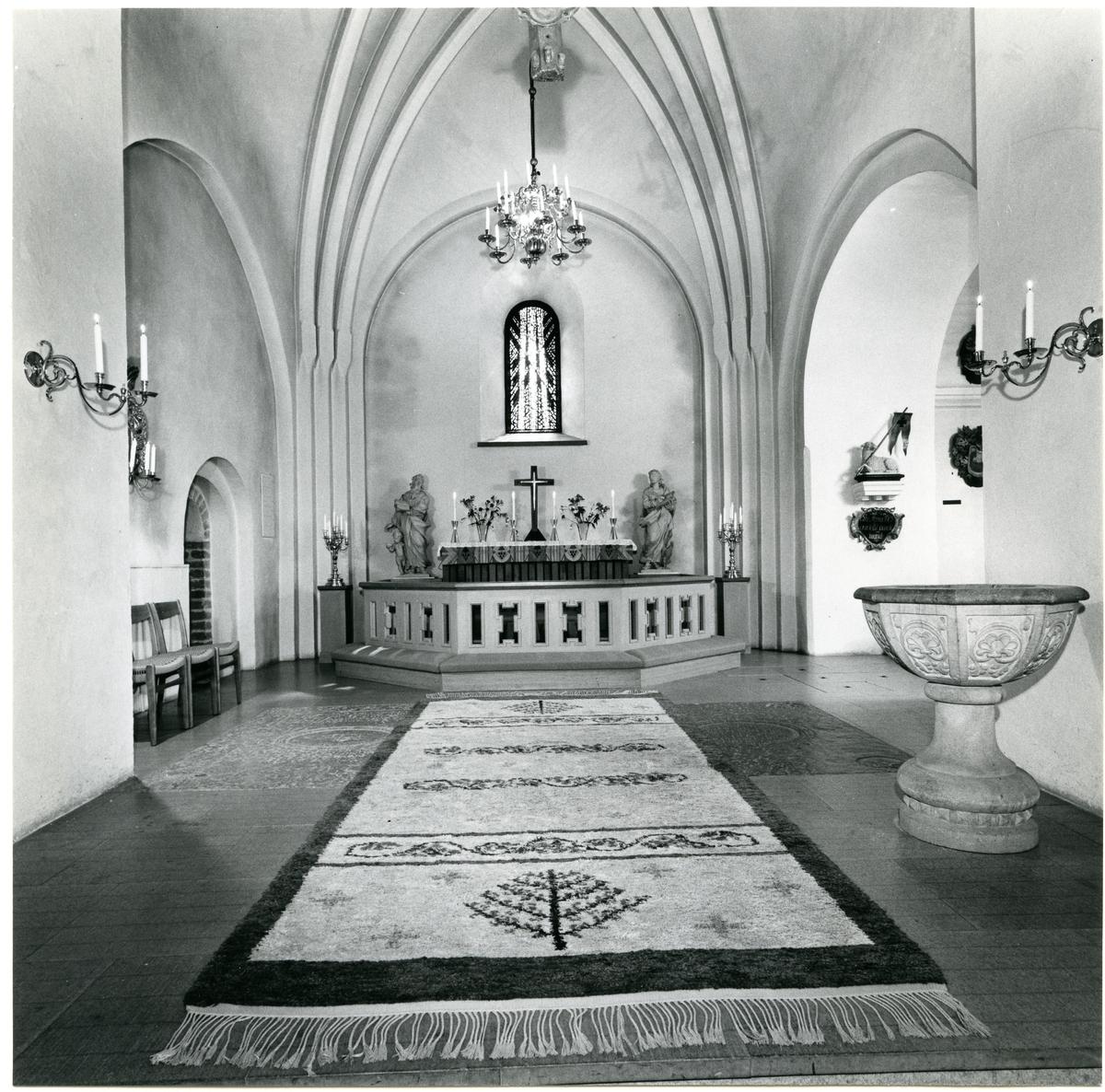 Badelunda sn, kyrkan. Interiör med altaret, dopfunt, matta m.m., 1983.