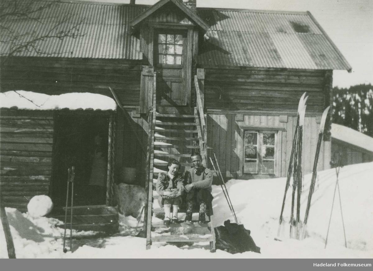 Elsa Hagen og Martin Hagen på trappa foran hytta på Trantjern, påsketur på ski