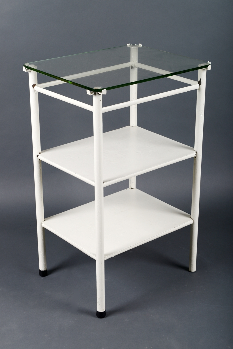 Bord/operasjonsbord laget av metall og glass. Bordet har en ramme av hvitmalt metall. Topplaten er laget av glass. Den er firkantet med avrundede hjørner. Det er to hyller under, begge tynne og laget av hvitmalt metall. Disse hyllene hviler på tynne metallstenger som er en del av bordets skjelett. Bordet har fire runde bein og det er svart gummi nederst på beina.