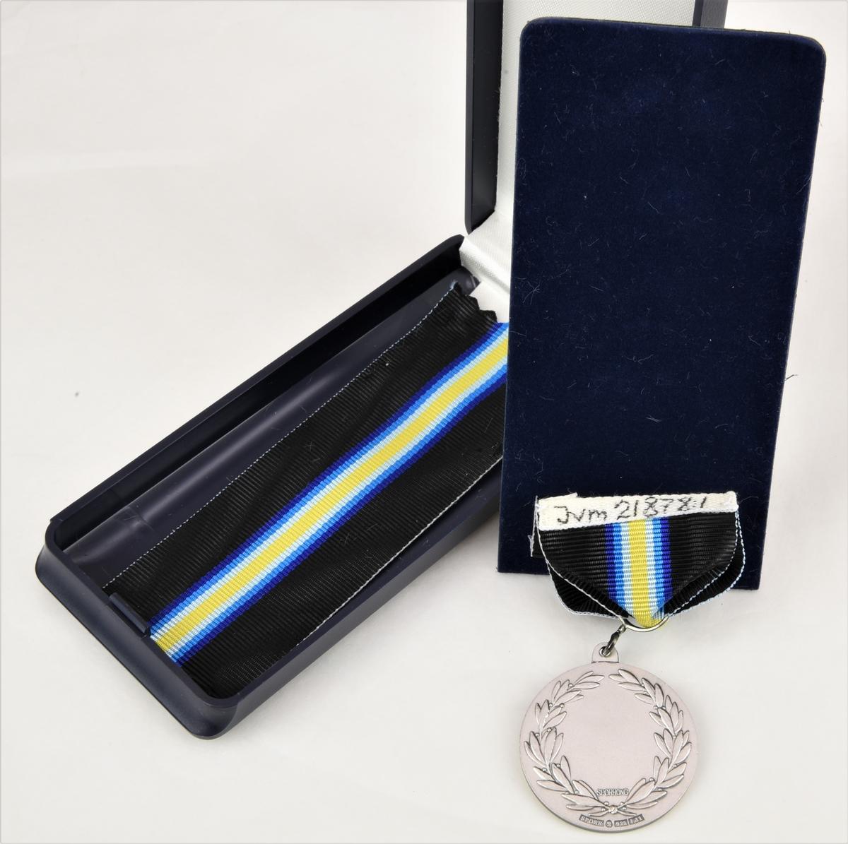 En silvermedalj från Driftvärnet som har ett svart band som pryds med en gul rand som omges på vardera sidor av tre ränder i olika nyanser av blått. Medaljens motiv är i relief och föreställer det krönta vinghjulet. Medaljens baksida omges av en lagerkrans med plats för inristning. Medaljen fästs vid klädseln med hjälp av två nålar som man knäpper fast baktill med varsin hatt.   Medaljen förvaras i ett avlångt blått etui som är gjort av plast. Lockets insida är prytt med vitt tyg av sammet medan etuiets botten är täckt med en blå mjuk plastfiber. Under botten finns ett reserv band.