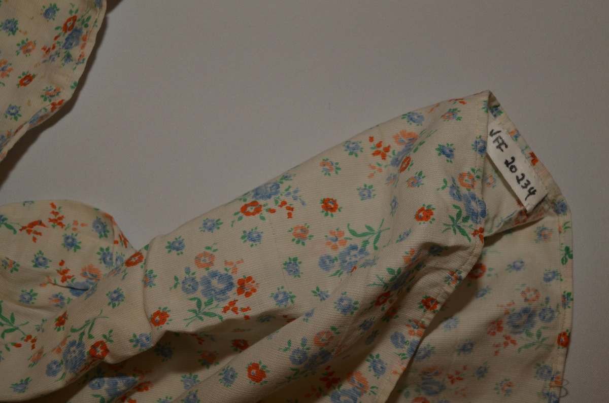 Kjole, barnekjole, sydd i småblomstra bomullstøy. Opning bak med tre kvite knappar. Bærestykke påsett rynka skjørt. Lang erm.
