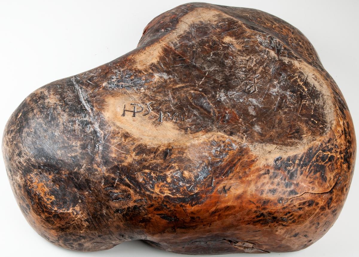 Träskål, vrilskål, snidad av utväxt från träd. Av björk, urgröpt, naturvuxen, ojämnt trekantig till formen. Undersidan märkt med karvsnitt: HPS 1864.