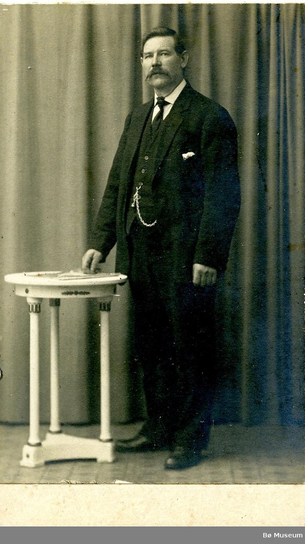 Atelierfoto av ein ukjent mann ståand ved eit bord.