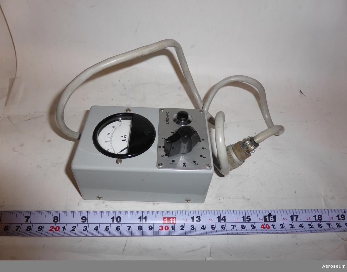 En Kontrollbox i brun läderväska, tillsammans med 2 mättabeller. Till för RA 800. I väskans läder är Tre kronor inpressat och i kontrollboxen sitter det fast en grå sladd.