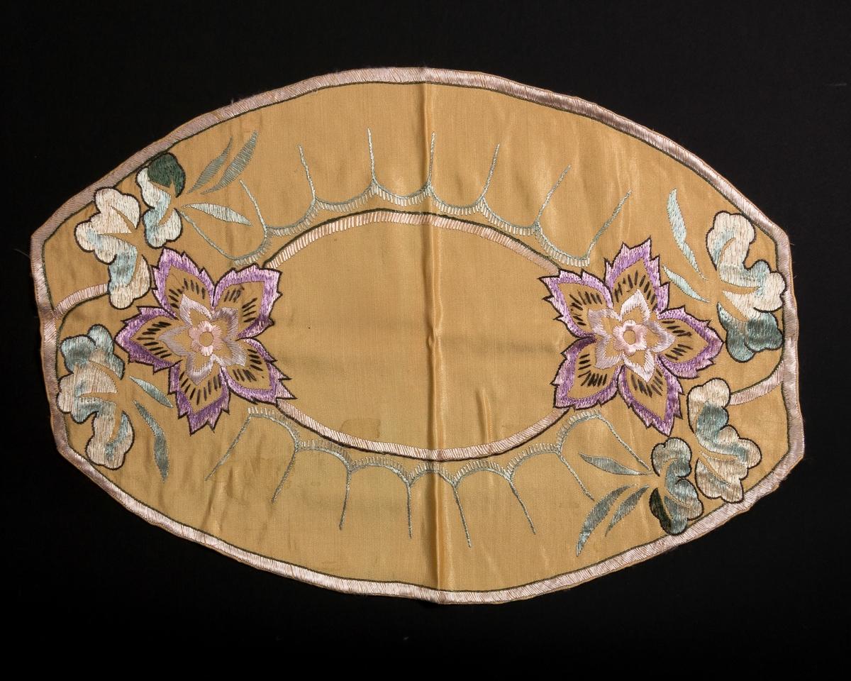 Oval duk i matt gult silkestoff. Dekorert med broderi: lilla blomster og border.