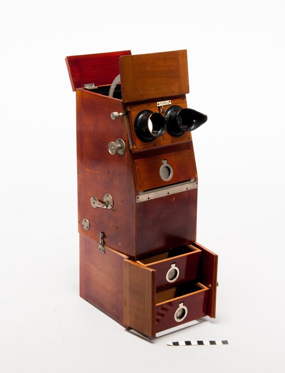 """Stereoskop för bilder 5 x 10 cm, med inställning för ögonavstånd och automatisk bildväxling samt magasin för 80 st bilder.  Nr instansat under toppluckorna: """"752376"""".  Ena ögonmusslan skadad. Bottendelen innehåller 4 stycken bildkassetter."""