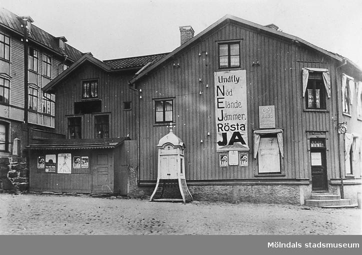 Kvarnbygatan 45 vid Gamla Torget i Mölndals Kvarnby, år 1922. Fasaden är affischerad inför förbudsomrösningen. 55,1 % röstade. Ja fick 49 % (förbud) och nej 51 %. Framför huset står en telefonkiosk. AF 1:12.