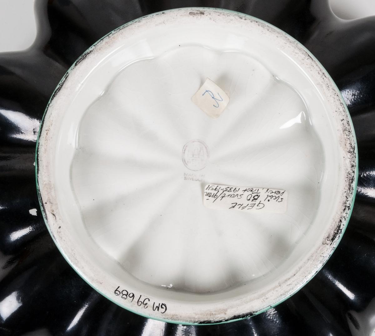Skål med välda sidor, svart utsida och grön insida som även är dekorerad med blomma i botten och gyllene kryss i sidorna. Förgylld kant.  Etikett under: GEFLE Skål, BO svart/grön Percy/Trost 1933-1934