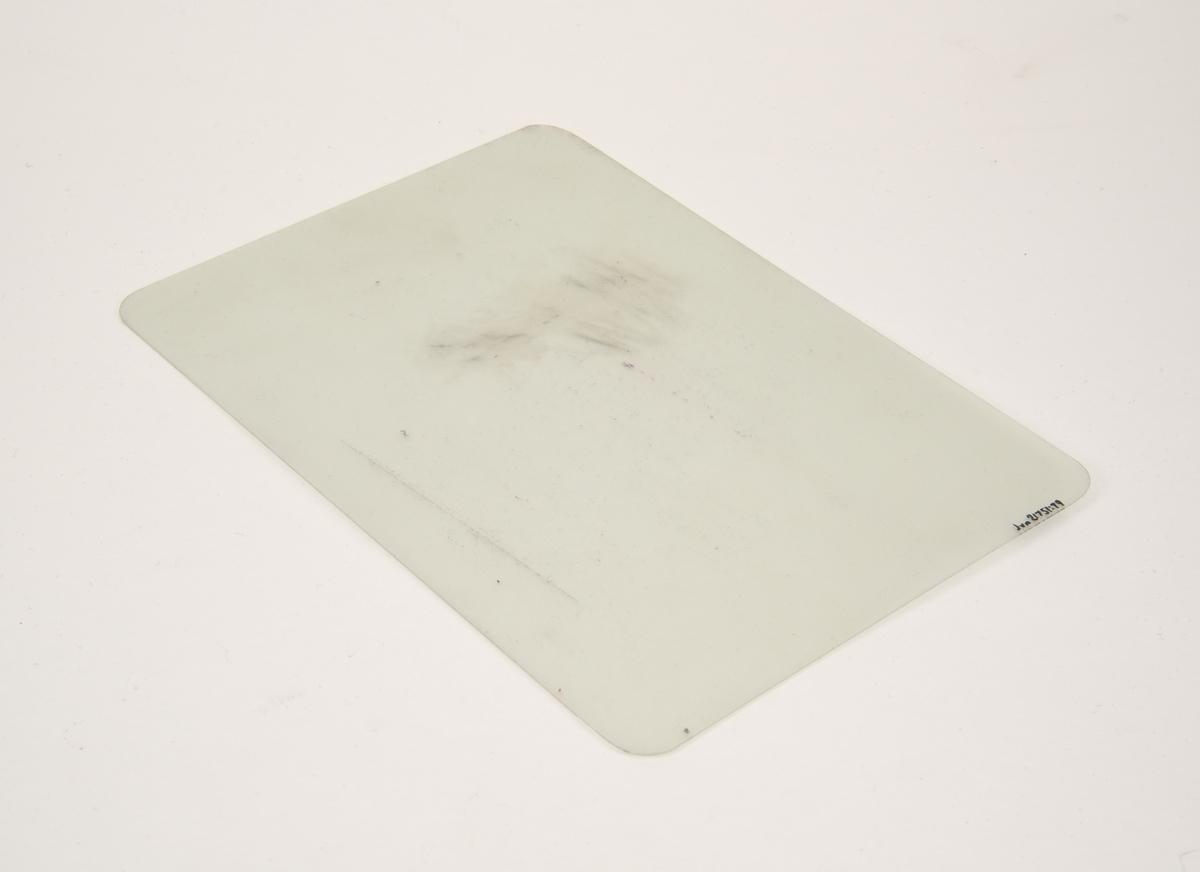 """Skrivplatta i A5-storlek av cellulosaplast. Plattan är böjlig, transparent och rektangulär med rundade hörn. Ena sidan är matt, den andra blank. Plattan ligger i ett kuvert av brunt papper med mörkblått tryck med bland annat Pelikans logotyp och """"SCHREIBPLATTE"""". På baksidan finns instruktioner på engelska om hur plattan ska användas."""