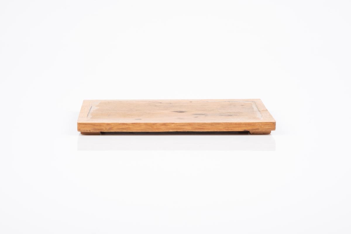 Bunnplate til treskrin. Har vært limt til bunnen av skrinet. Bunnplaten står på 4 ben (tynne kvadratiske klosser).