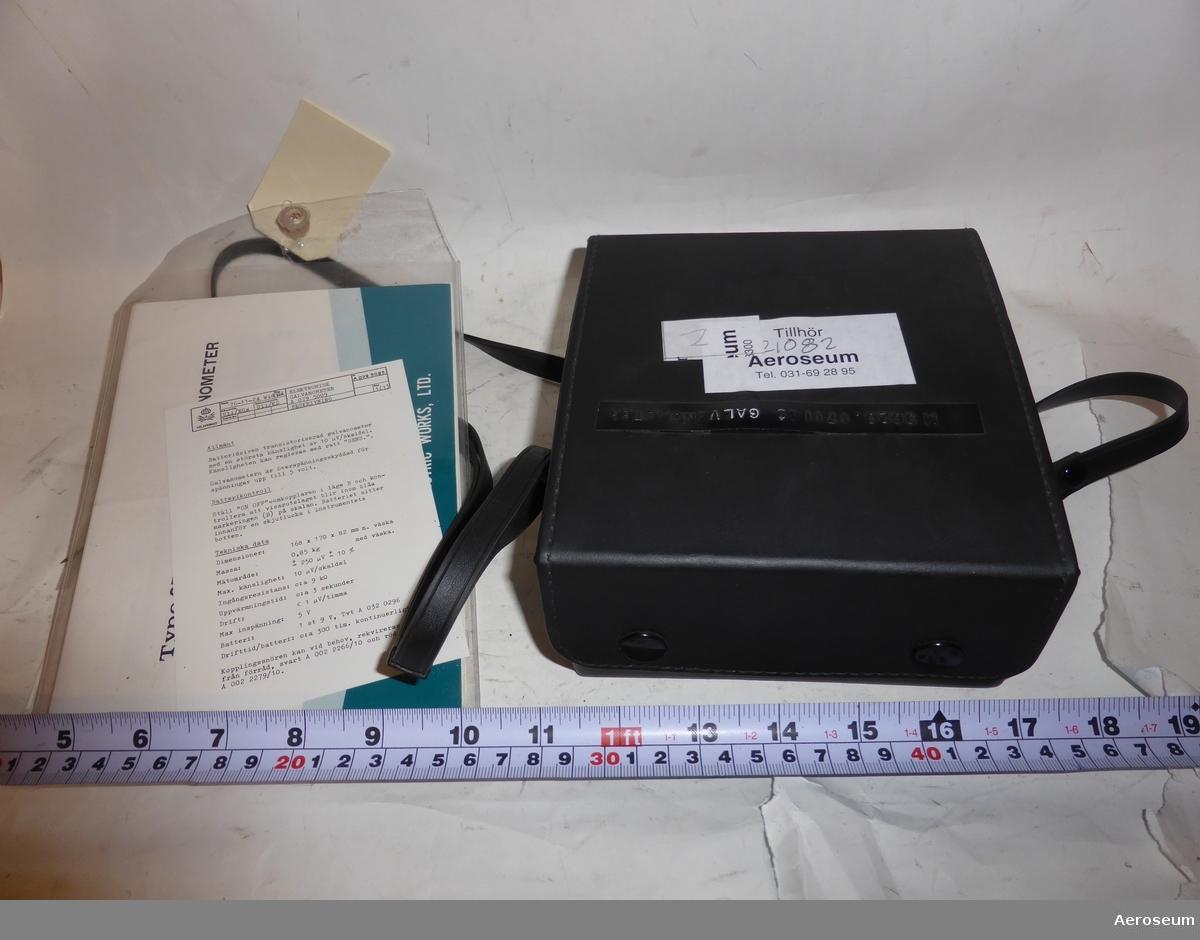 En galvanometer i en svart läderväska. I en plastficka som sitter fastsatt i väskans bärrem finns det en manual på engelska, en lapp med instruktioner på svenska, och en extra manual för en mätspänningskälla. Galvanometern är tillverkad av Yokogawa Electric Works, Ltd. i Japan.