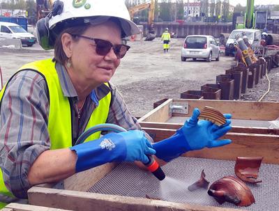 Arkeolog og funnansvarlig Susanne Pettersson i såldet -  med et tidstypisk skår i vårt undersøkelsesområde av havna; keramikk produsert i Weser-distriktet i Tyskland på sent 1500-tall. (Foto: NMM)