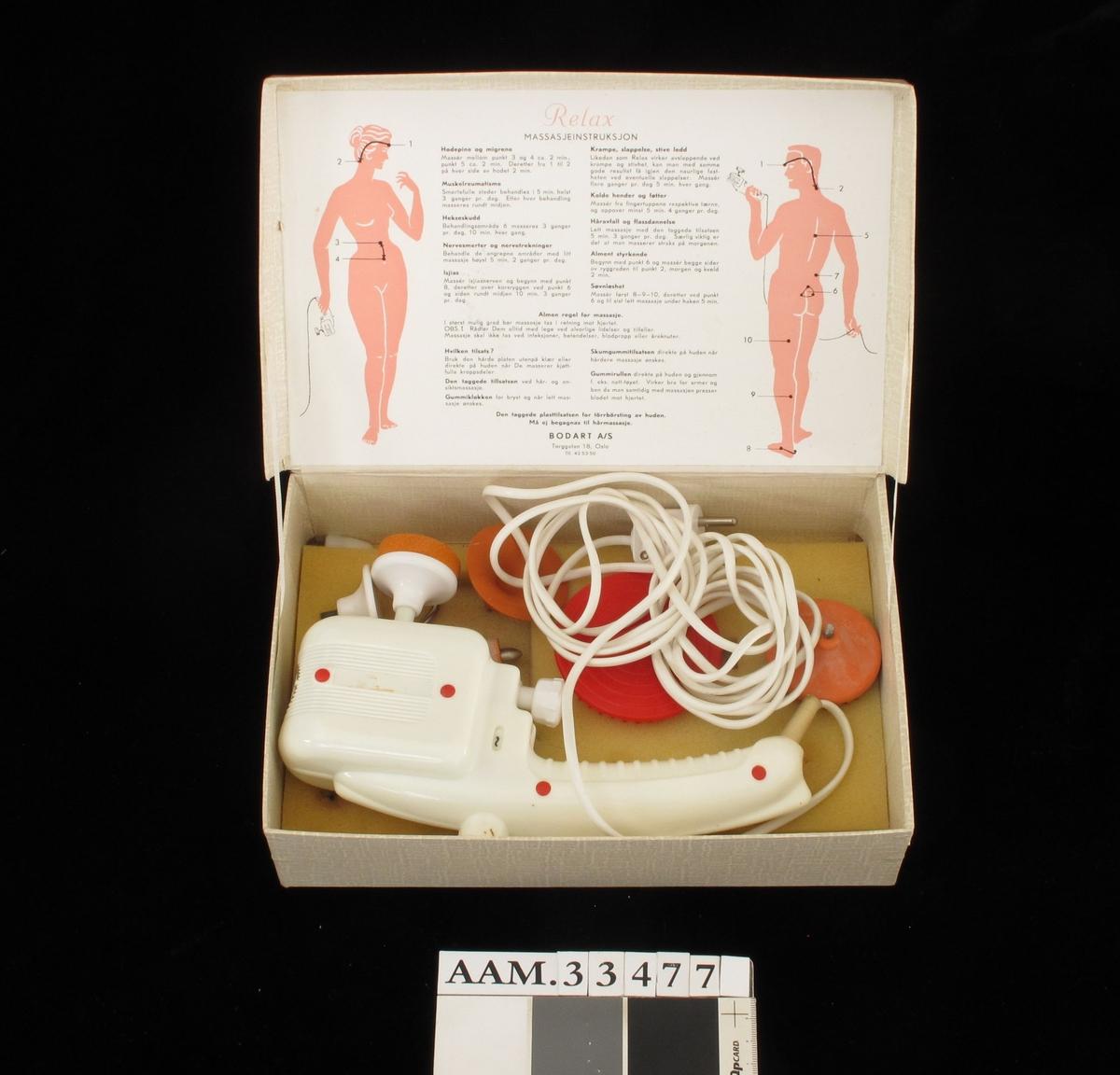 Eske med elektrisk massageapparat. Apparat i gulhvit plast. I alt 5 ulike redskaper.  Lokkets innside med bruksanvisning.