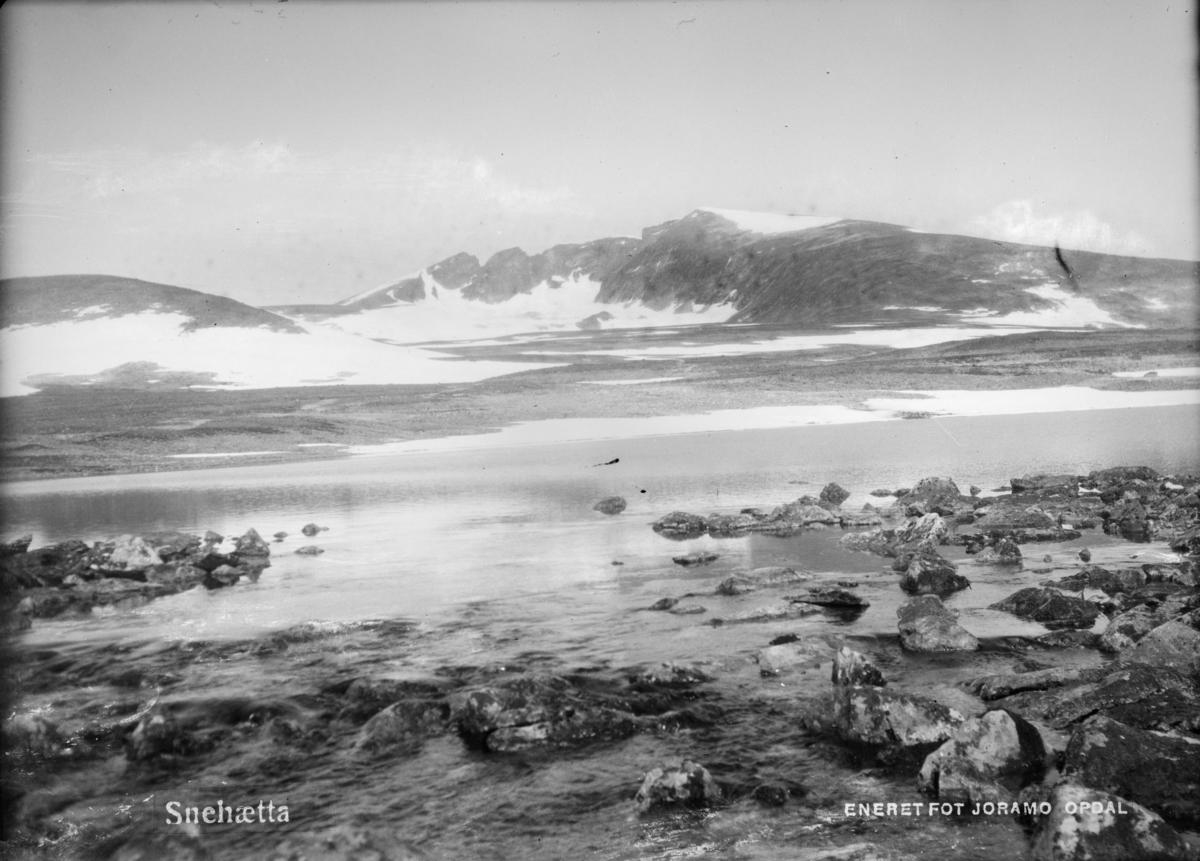 Dovrefjell med Snøhetta og vann i forgrunn. Påskrift: Snehætta