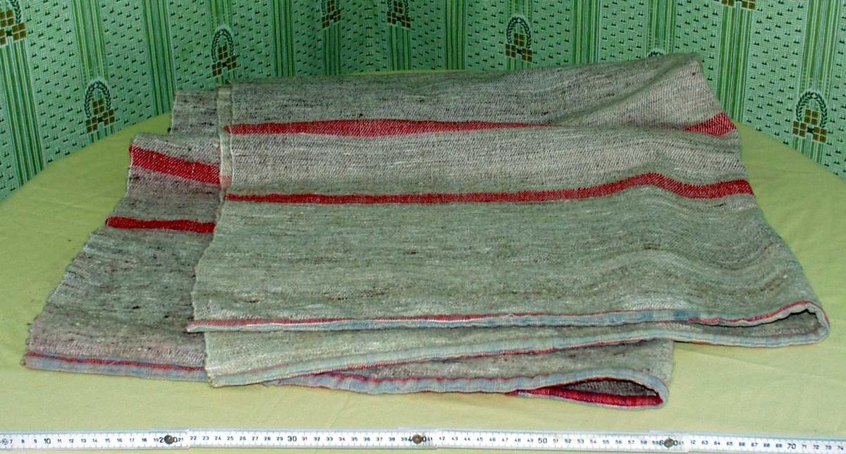 Vevd sengeteppe i ull. Hovedfarge grå, med røde og blå tverrstriper.