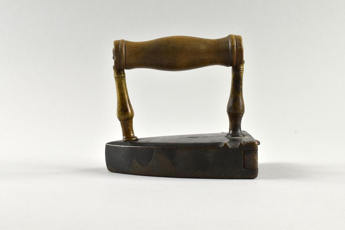Lodstrykjärn av stål med ståndare av mässing och svarvat handtag av trä. På järnet sitter en öppningsbar lucka för lodet. Ett rostigt lod av järn, målat i blågrått, ligger i.
