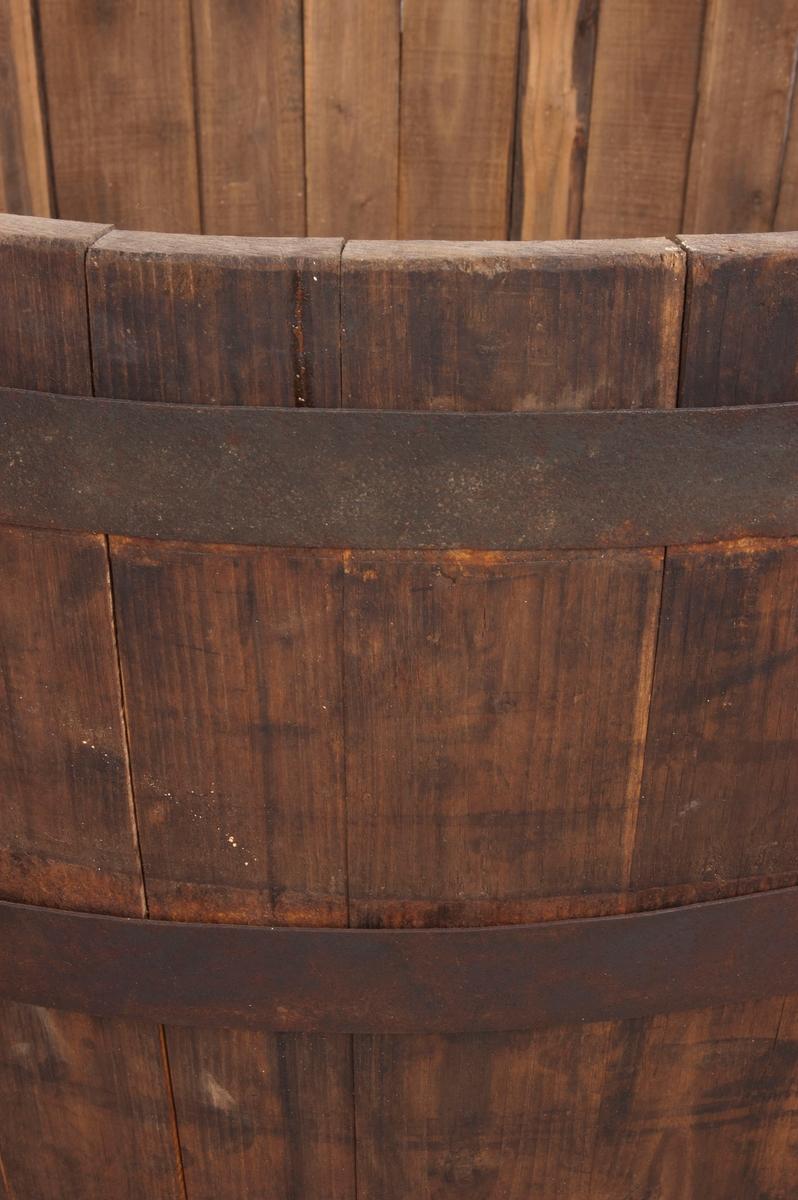Rund stamp av treverk, festet sammen ved hjelp av metallbånd. To håndtak av annet metall-materiale enn båndene. Mulig av nyere dato. Stampen består av 36 staver og fire metallbånd. Bærer preg av slitasje/alder.