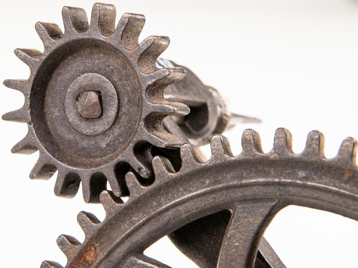 Äppelskalare av järn, gjutna delar. Försedd med vev med ett svarvat trähandtag som driver två kugghjul mot varandra, ett större och ett mindre. En vingmutter finns för att sätta fast skalaren i ett bord. På ena hjulet finns en kniv för skalning och på det andra piggar att fästa äpplet i. en av delarna har ett ingjutet F.