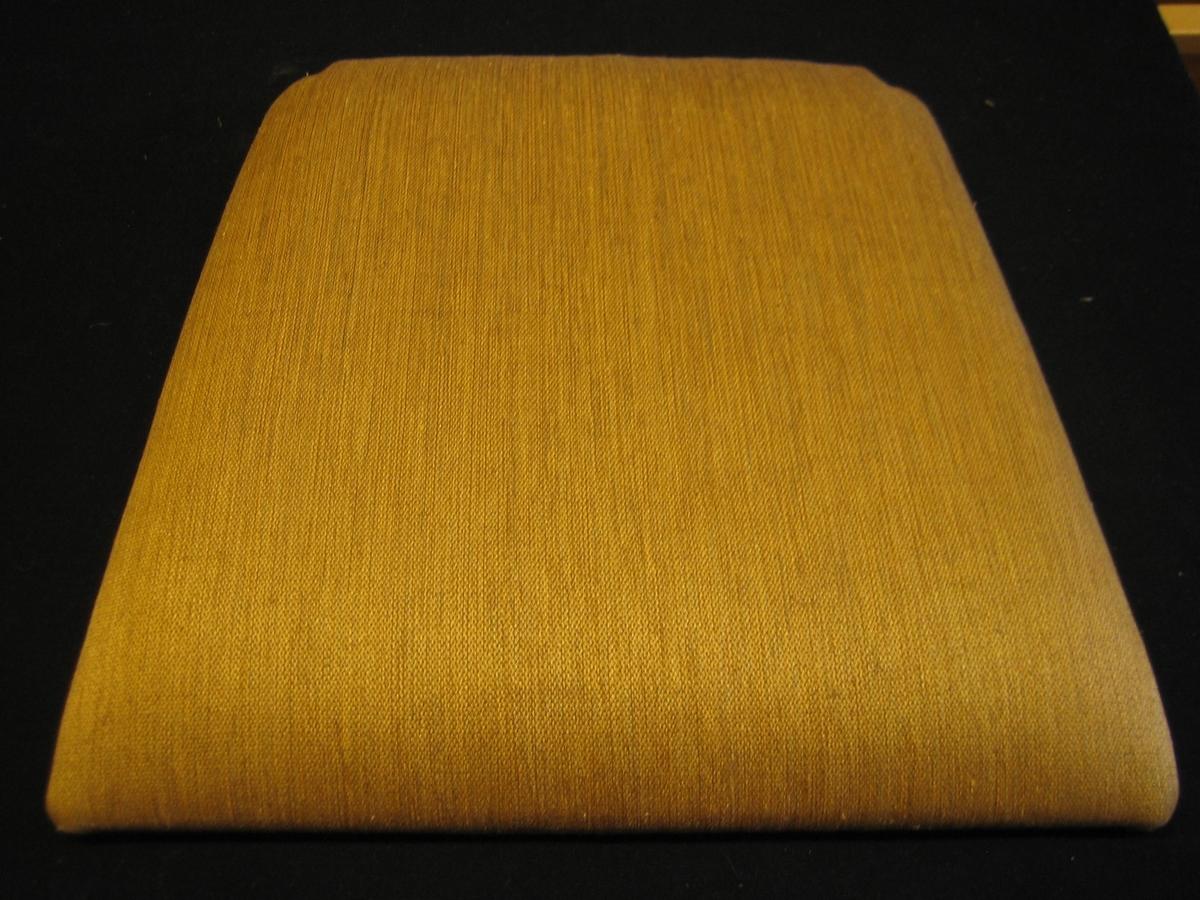 """Möbelöverdrag, möbeltyg monterat på stolsdyna. Ett stadigt möbeltyg i kypert. Tyget är enfärgat. Varpen är brunt bomullsgarn. Inslaget är gult lingarn i olika nyanser. Möbeltyget är monterat med häftklammer på en stolsdyna av skivmaterial av trä med stoppning. Dynan är lite smalare i bakkant och där är hörnen urtagna.  På undersidan sitter en vit klisterlapp med texten: """"Möbeltyg Kvalitet: Inslag - lin, varp - bomull Bredd: 128 cm Pris 430:-"""" och en lapp med texten:""""SKARABORGS LÄNS HEMSLÖJDSFÖRENING"""" och ytterligare en lapp med texten: """"TRÄ-TINA Storekvarn pl 397 540 17 LERDALA 0511-804 64"""""""