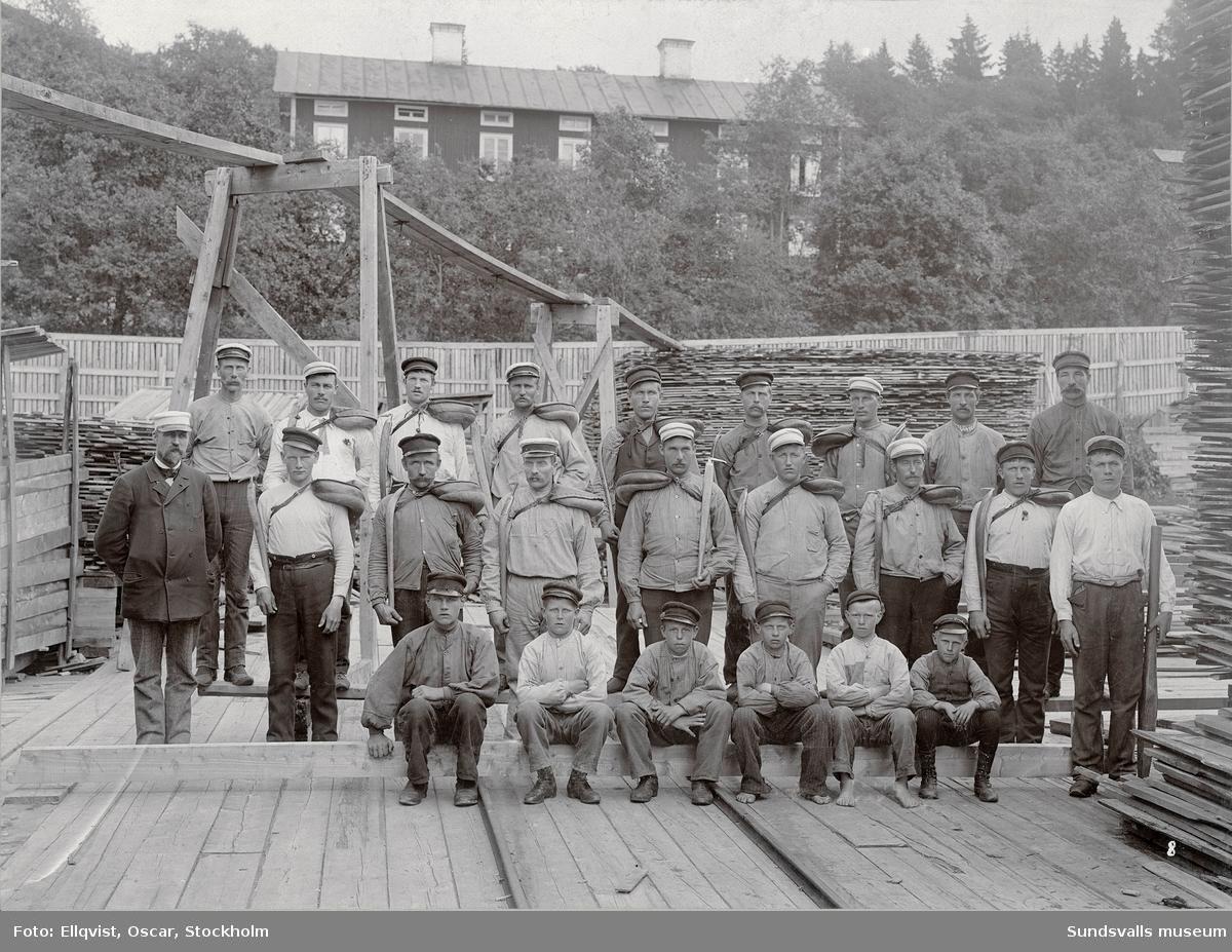 Brädgårdsarbetare, Fagerviks sågverk. I bakgrunden en av arbetarbostäderna. Per Aron Landin  (f. 1867 d. 1946) står i översta raden 4:e man från höger. Landin blev senare handelsföreståndare i Fagervik.