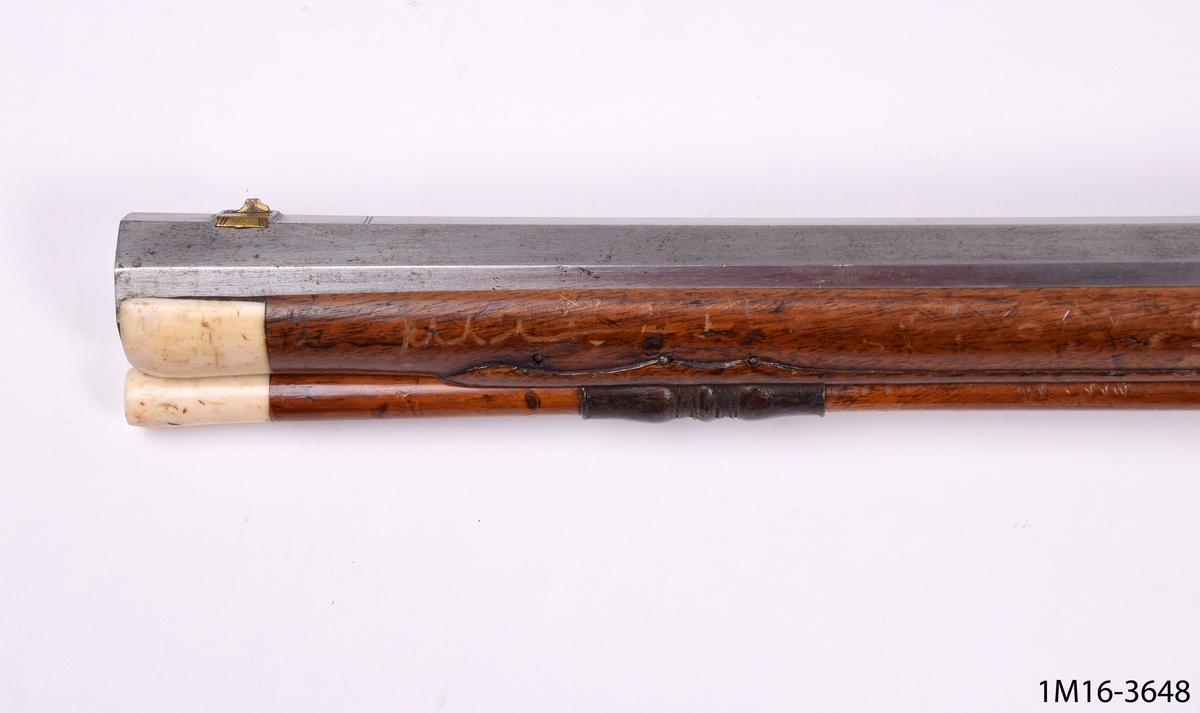 Hjullåsgevär av trä och metall. På trädelarna finns reliefdekor föreställande bland annat snäcka, blad och blommor